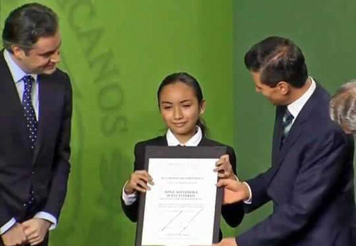 Nina Alejandra Poot Esteban, de Bacalar, recibiendo el reconocimiento de manos del presidente, Enrique Peña Nieto. (Facebook)