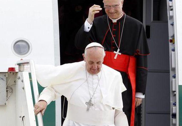 El Papa a su llegada a Roma aparece en compañía del secretario de estado del Vaticano, cardenal Tarcisio Bertone. (Agencias)