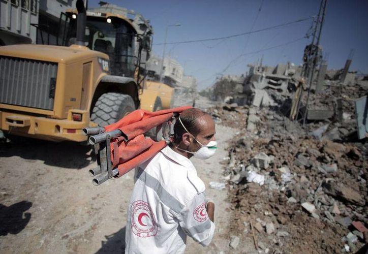 Personal de la Media Luna Roja (equivalente a la Cruz Roja) busca heridos, tras los bombardeos de Israel, en el barrio Shijaiyah, de la Ciudad de Gaza. Según los palestinos, 682 personas han muerto en las ofensivas hebreas de las últimas 2 semanas. (AP)
