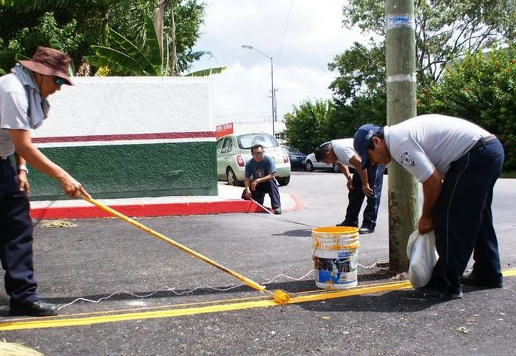 La Subdirección de Tránsito realiza labores de señalización afuera de las escuelas de Cozumel. (Cortesía)