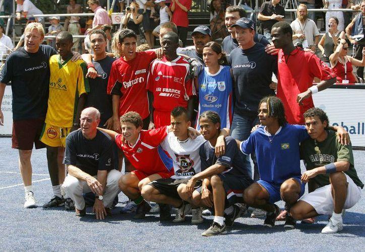 El veterano Bobby Charlton (abajo 1º izda) y el extenista Boris Becker (arriba 1º izda) en el Mundial de Fútbol Callejero en el que participaron 22 equipos surgidos de proyectos sociales en zonas marcadas por marginación, conflictos armados o pobreza. (EFE/Archivo)