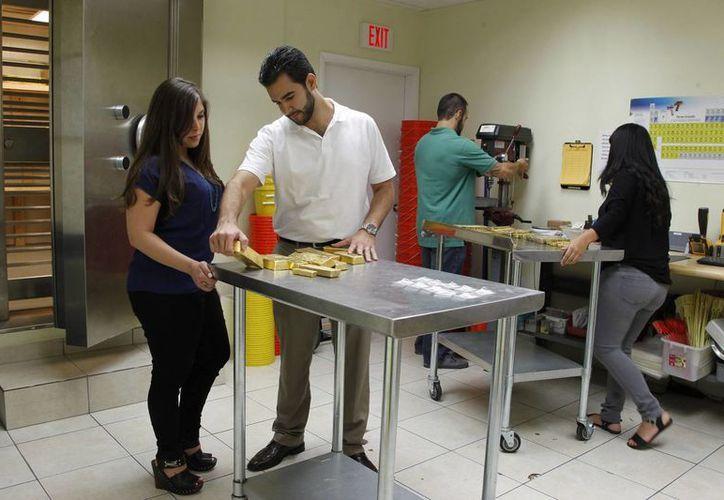 Jenna Kaloti-Ramirez (I) y su esposo Jorge Ramirez (c) durante la revisión de un cargamento de oro en el negocio de ambos. (Agencias)