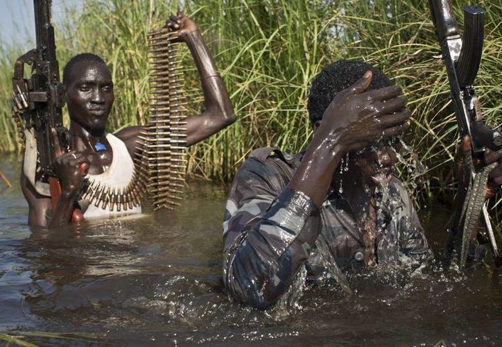 Soldados rebeldes protegen a los civiles en una zona pantanosa en su camino a un campo de refugiados de la Acnur en Sudán del Sur. (Agencias)