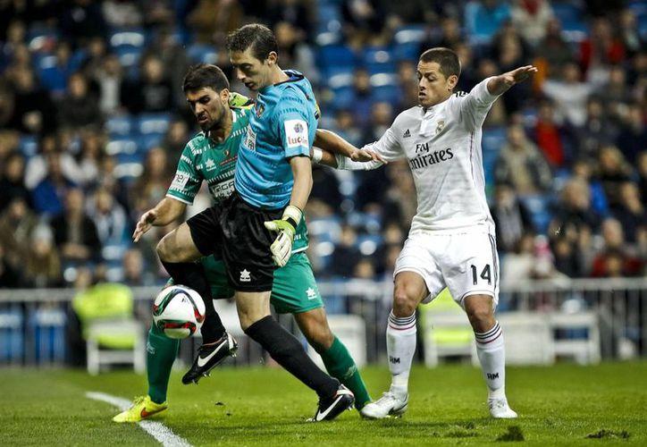 El mexicano Javier Hernández, Chicharito (d) lucha por el balón en partido de dieciseisavos de final de Copa del Rey ante el modesto Cornellá. (EFE)