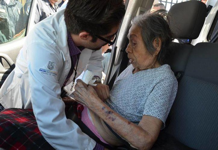 Imagen de una anciana al momento de ser atendida por un paramédico durante su rescate. El asilo Hermoso Amanecer se incendió ayer en Mexicali, Baja California. (EFE)