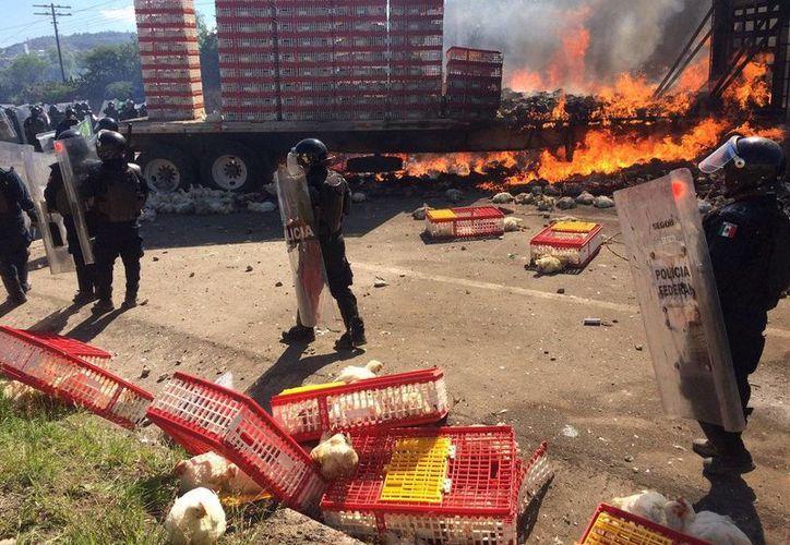 La Policía Federal realizó un operativo para desalojar a los docentes en el crucero de Nochixtlán; manifestantes incendiaron un camión doble remolque, que trasportaba pollos en pie de cría, para ser usado como barricada. (@kikesma)