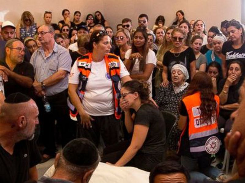 Relatives and friends gather around the body of Yotam Ovadia during his funeral in Jerusalem. (AP)