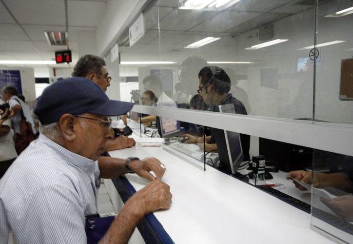 La ley marca una pensión mínima para un jubilado de 2,500 pesos mensuales, y solo el 50 % de los ahorradores estaría en ese nivel, cifra insuficiente para solventar necesidades de los retirados. Imagen de contexto de un anciano en una sucursal bancaria. (Archivo/SIPSE)