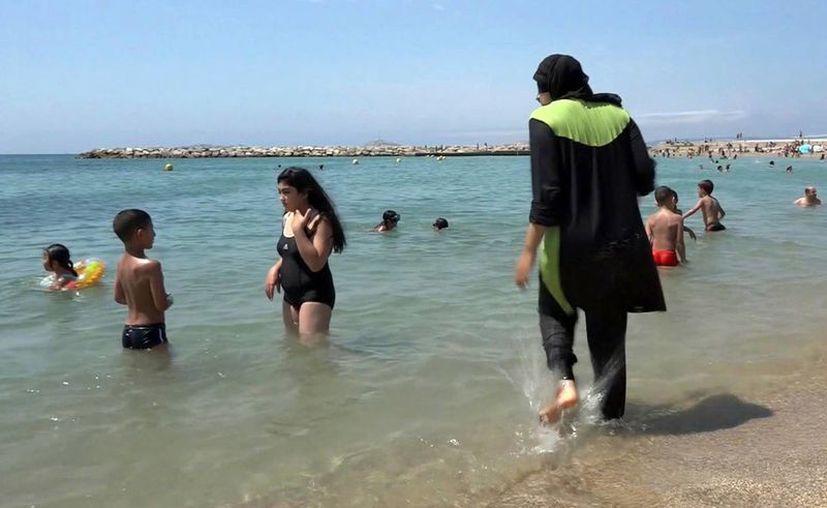Imagen tomada de un video, en la que se ve a Nissrine Samali, de 20 años, metese en el agua vistiendo un burkini, un traje de baño completo que cubre de pies a cabeza, en Marsella, en el sur de Francia. (AP)
