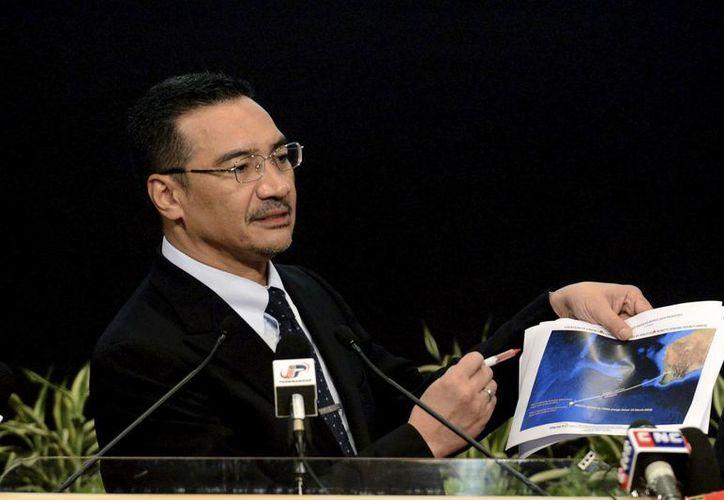 El ministro de Defensa malayo, Hishammuddin Hussein, muestra una gráfica de los más recientes objetos detectados por satélite que podrían corresponder al vuelo de Malasia desaparecido desde el 8 de marzo. (Agencias)