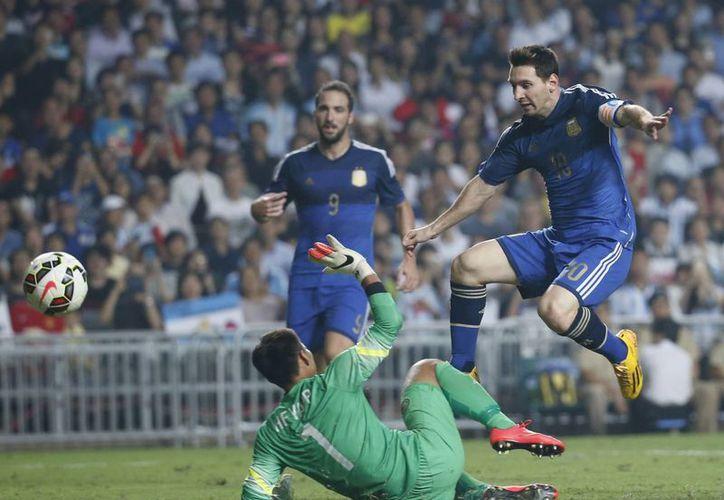 Messi, uno de los mejores jugadores en la historia de la Selección de Argentina, al momento de enviar la pelota al fondo de las redes de la portería de Hong Kong en partido amistoso que terminó 7-0. (Foto: AP)