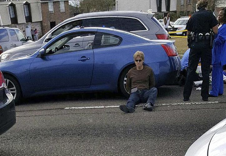 Ronald Gasser (sentado sobre el pavimento) poco después del tiroteo en el que murió Joe McKnight, jugador de la NFL. Gasser está acusado de homicidio. (AP)