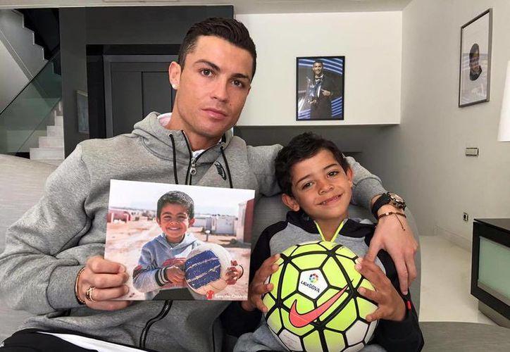 En imagen, CR7 junto a su hijo de cinco años sosteniendo la foto de Ayman, un niño refugiado sirio apasionado por el futbol. (Facebook: Cristiano Ronaldo)
