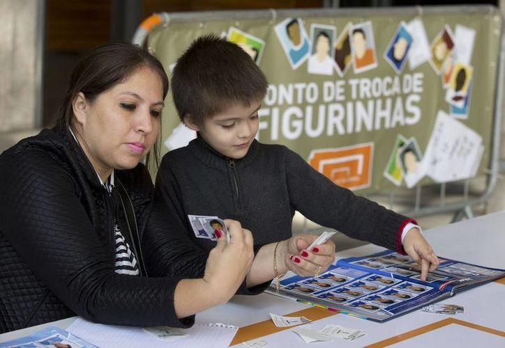 Una mujer y su hijo organizan su colección de láminas autoadhesivas del álbum de la Copa del Mundo en una mesa de intercambio afuera del estadio de Pacaembu, en Sao Paulo, Brasil. (AP)