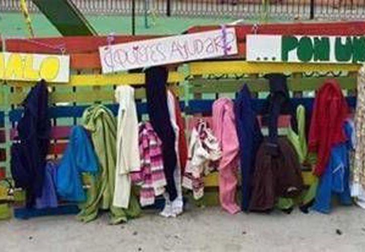 Estudiantes de la Universidad Marista se unen a #SinFrio campaña que se ha difundido en redes sociales para obsequiar ropa de abrigo a quienes lo necesiten. Las prendas han sido colocadas en el parque de San Juan, en Mérida. (SIPSE)