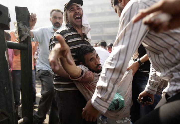 Partidarios de Morsi evacuan a un herido durante los enfrentamientos con las fuerzas de seguridad egipcias en la plaza de Ramsés. (Agencias)