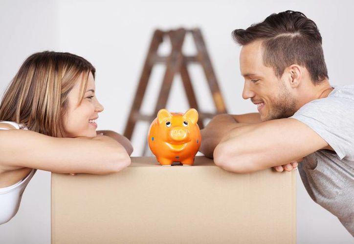 Exhortan a los trabajadores a saldar deudas pendientes o en su caso de realizar compras inteligentes. Imagen de una pareja que mira sus ahorros en una alcancía. (Agencias)