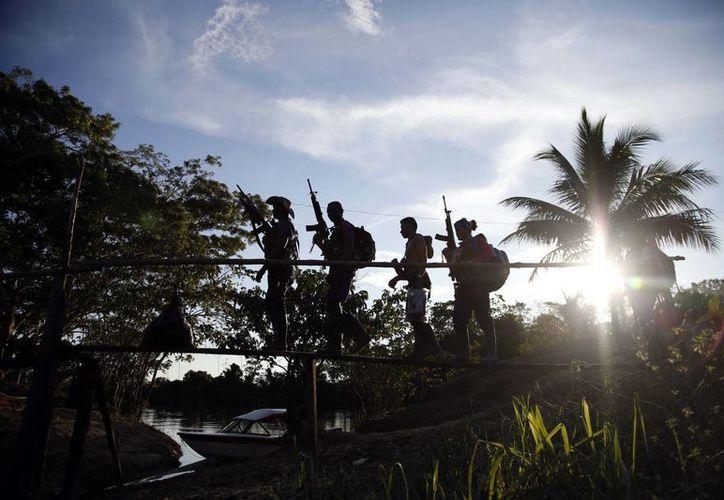 Las FARC se volvieron impopulares cuando en las últimas décadas comenzaron a secuestrar, extorsionar y cobrar impuestos a la producción de cocaína. Foto de los rebeldes del frente 48 de las FARC al pasar por un puente en la selva del sur del Putumayo, Colombia. (AP/Fernando Vergara))