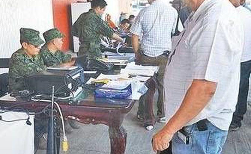 Decenas de ganaderos y campesinos hicieron fila para entregar documentación a la Sedena y recibir su certificado médico. (Milenio)