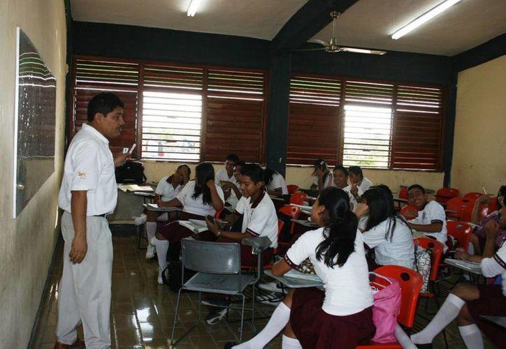 Los egresados que aún no están titulados, la ENSY ofrece un taller para obtener el grado de profesor. En la imagen un maestro durante una clase en Mérida. (Milenio Novedades)