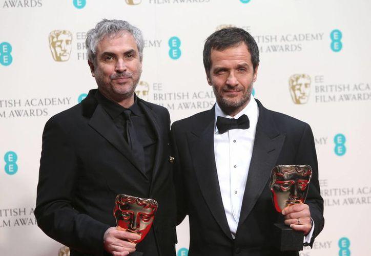 El director Alfonso Cuaron acompañado del productor David Heyman, ambos ganadores por la cinta Gravity en el BAFTA. (Agencias)