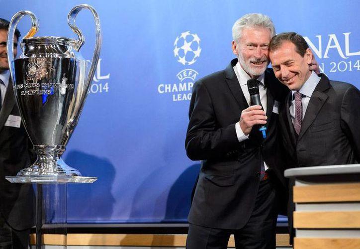 Paul Breitner (izq.) representante del Bayern Munich bromea con Emilio Butragueño, del Real Madrid, durante el sorteo de semifinales de la Liga de Campeones de Europa. (AP)
