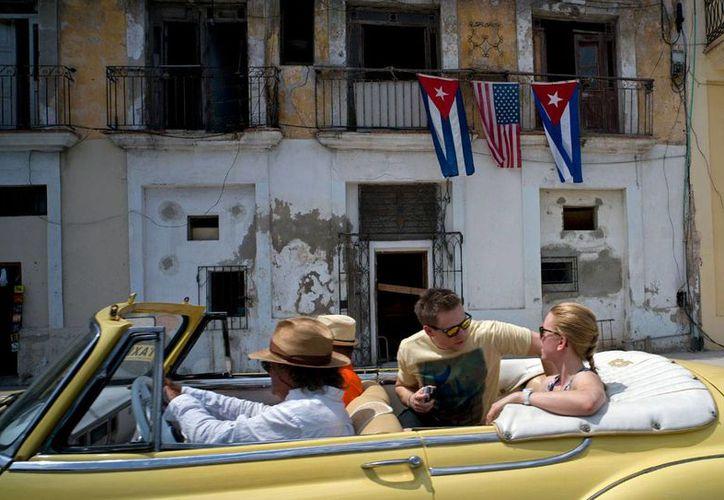 Imagen del 20 de marzo de 2016, de turistas norteamericanos paseando en un auto clásico en La Habana, Cuba. El gobierno de la isla informó el martes 27 de diciembre de 20126, que el país entró en recesión al contraerse 0.9 % el PIB, en 2016. (AP/Ramón Espinosa)