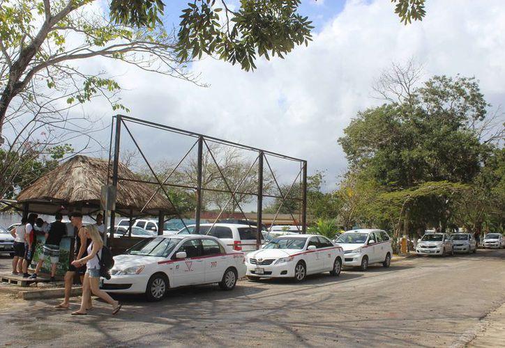 Los taxis y las camionetas foráneas se parquean en espera de turistas. (Sara Cauich/SIPSE)