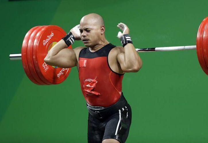 Bredni Roque Mendoza, de México, al dejar caer la barra durante su participación en la competencia de levantamiento de pesas 69 kg masculino en los Juegos Olímpicos de 2016 en Río de Janeiro, Brasil. (Foto AP / Mike Groll)