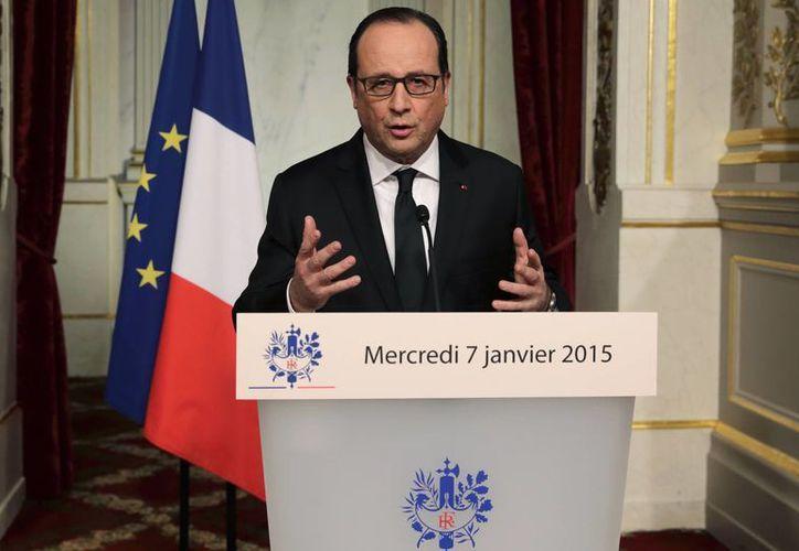 El presidente Hollande condenó el 'cobarde' ataque a los caricaturistas de la popular revista Charlie Hebdo. (AP)