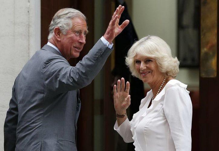 El príncipe Carlos y su esposa la duquesa Camilla, saludando durante una presentación en público. (Archivo Agencias)