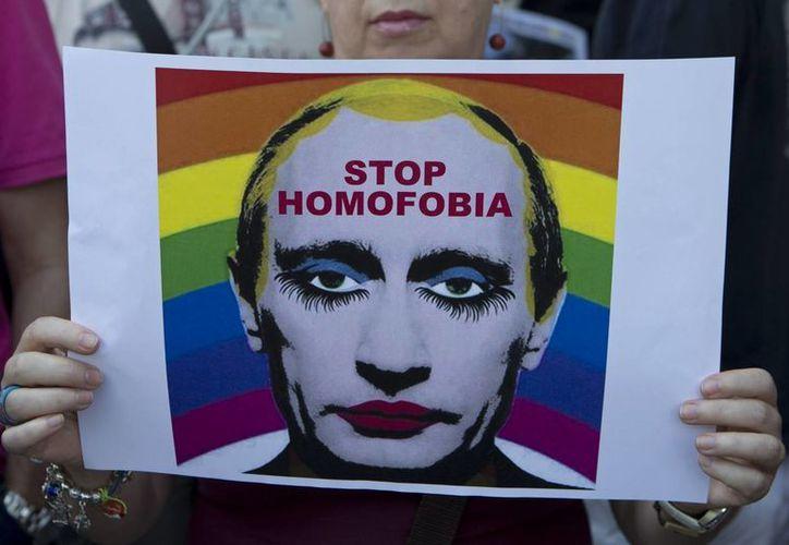 Una mujer sostiene un cartel que representa el presidente ruso Vladimir Putin durante una protesta frente a la embajada rusa en Madrid. (Agencias)