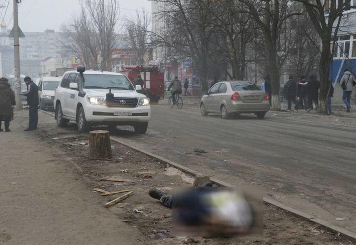Un cadáver yace en una calle de Mariupol, Ucrania, donde por lo menos 29 personas murieron en ataques discriminados con cohetes. (Agencias)