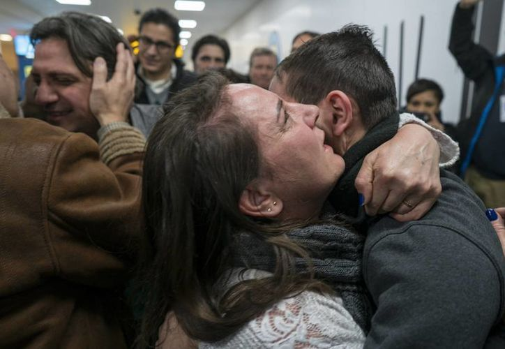 Familiares, algunos de ellos llegados desde Siria, se abrazan a otros residentes en EU a su llegada al aeropuerto internacional John F. Kennedy de Nueva York. (AP/Craig Ruttle)