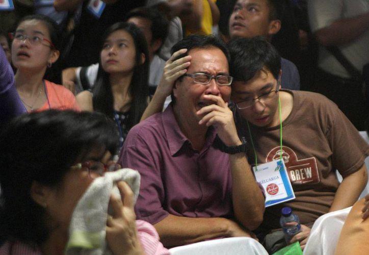Familiares de los pasajeros del vuelo 8501 de AirAsia lloran desconsoladamente, tras enterarse por la televisión de que el avión se estrelló en el mar. (AP)
