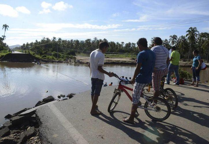 Autoridades trabajan a marchas forzadas para reparar zonas incomunicadas en Guerrero, como se aprecia en esta foto. (Agencias)