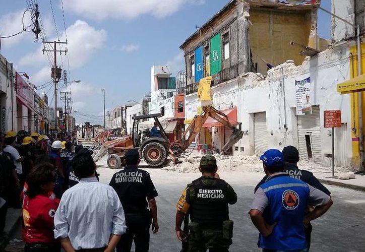 El regidor Rubén Segura Pérez observa el retiro de escombros en el edificio que se derrumbó el jueves en la zona de mercados de Mérida. (SIPSE)