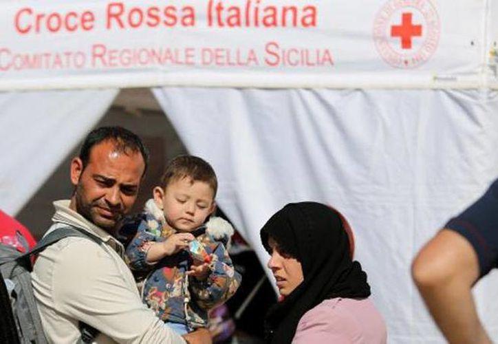 Una familia de inmigrantes espera afuera de una carpa de la Cruz Roja después de llegar al fuerte de Augusta, Sicilia, en el sur de Italia. (Agencias)