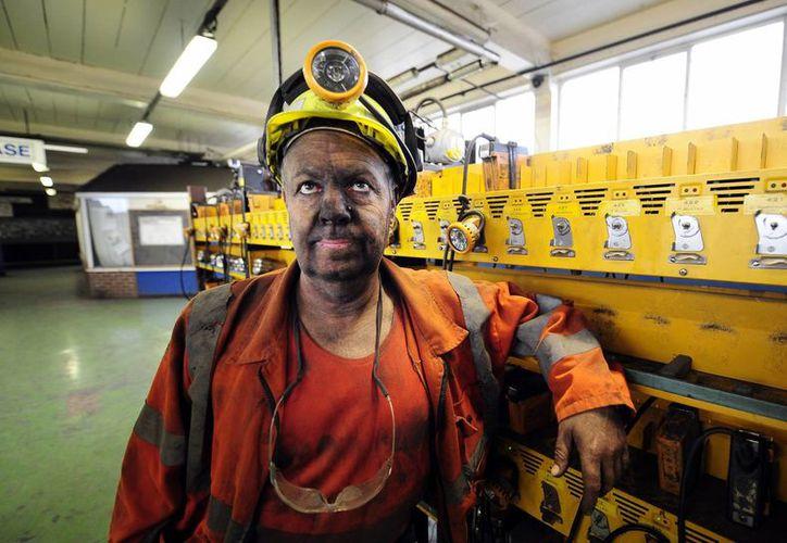El minero Phil Kelsey, quien trabajó en Kellingley Colliery en Knottingley, en el norte de Inglaterra, durante 32 años, deja la sala de lámparas al terminar el último turno. (Agencias)