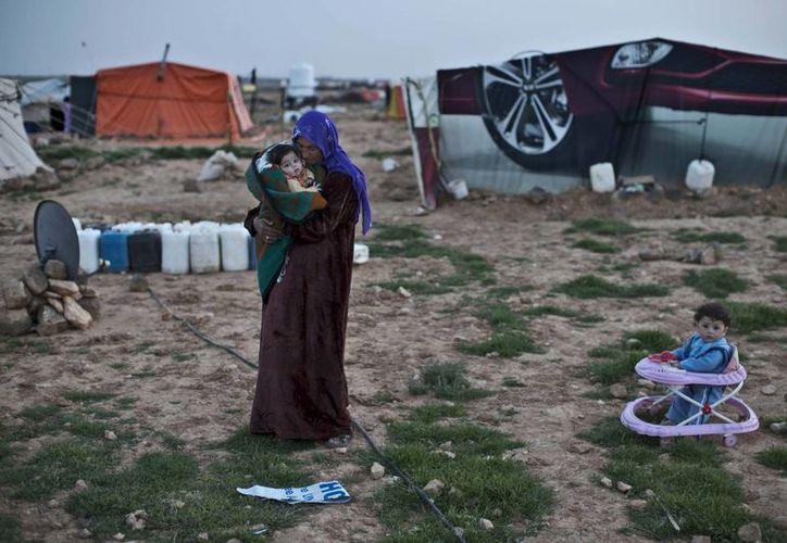 Imagen del 8 de marzo pasado, de una mujer siria con sus hijos en el campo de refugiados  Rifaa Ahmad. Los ataques del Estado islámico en aldeas sirias ha motivado la salida de miles de personas. (Foto: AP)