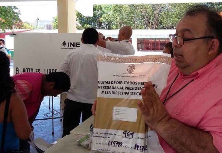 Jorge Martín Aldana y Ponce, secretario del Conesejo Distrital 01 en INE, con el  paquete electoral recuperado. (Daniel Pacheco/SIPSE)