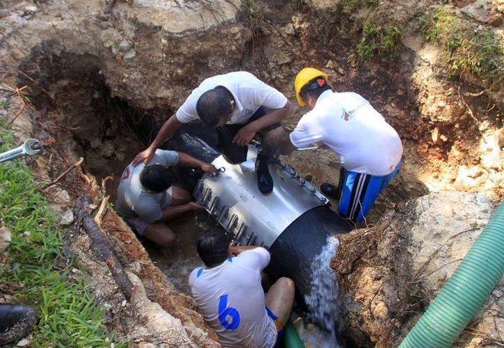 Trabajadores tratando de reparar la tubería rota ayer, en Chetumal.  (Harold Alcocer/SIPSE)