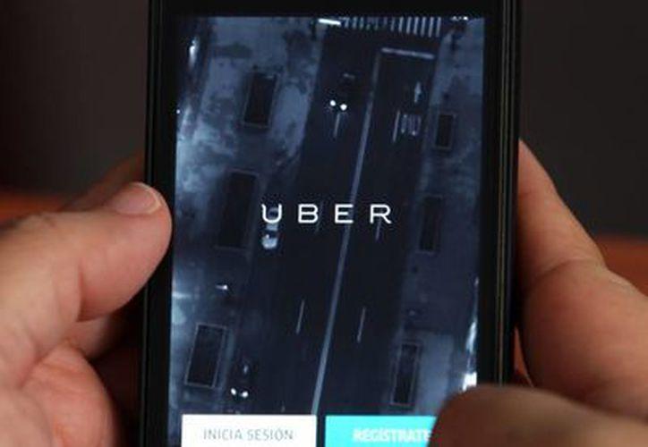Vista de un teléfono celular donde anuncia el servicio de le empresa Uber, la cual es demandada por tres trabajadores. (Archivo/EFE)