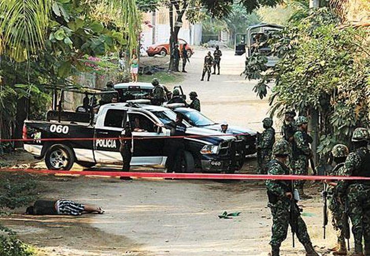 Militares y policías resguardan uno de los cadáveres que dejó la violencia en el puerto turístico. (Milenio)