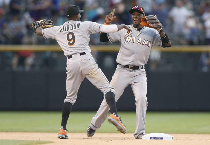 El shortstop de Marlins, Adeiny Hechavarria (d), celebra con su compañero, el segunda base Dee Gordon por su triunfo ante Rockies. (Foto: AP)