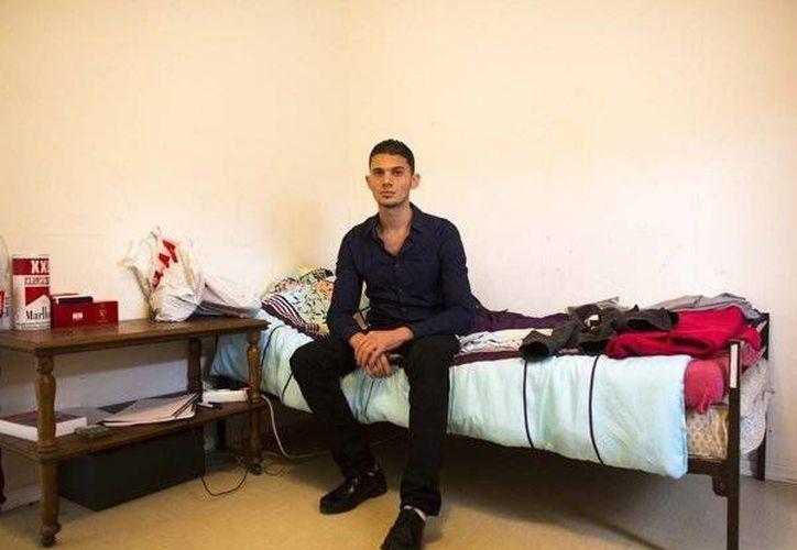Fotografía de Mohammad Suleimane sentado en su cama del refugio para solicitantes de asilo en Luebeck, Alemania. (Agencias)