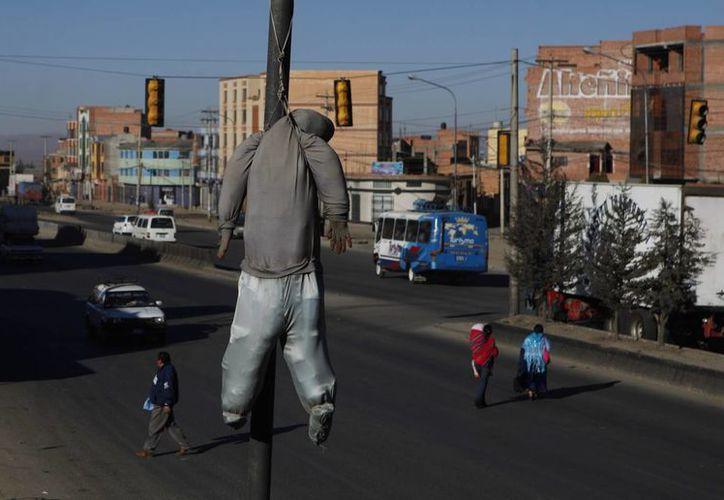 Un muñeco cuelga de un poste del alumbrado público como advertencia a delincuentes. (Agencias)