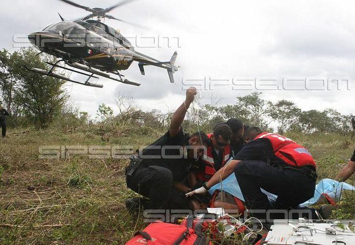 Paramédicos de la SSP atienden a la extranjera hallada en montes de la carretera Mérida-Valladolid. (Jorge Sosa/SIPSE)