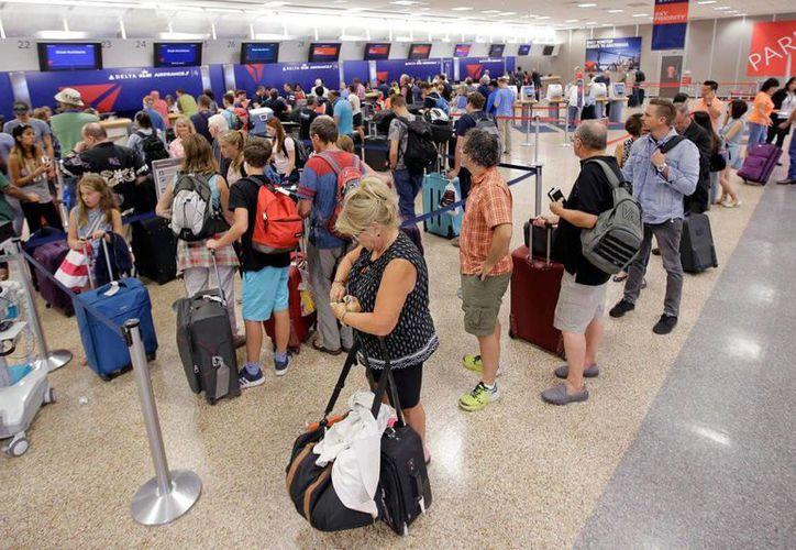 Pasajeros de la aerolínea Delta hacen fila tras la reanudación de los vuelos de la empresa luego de un fallo informático, en Salt Lake City. (AP Foto/Rick Bowmer)