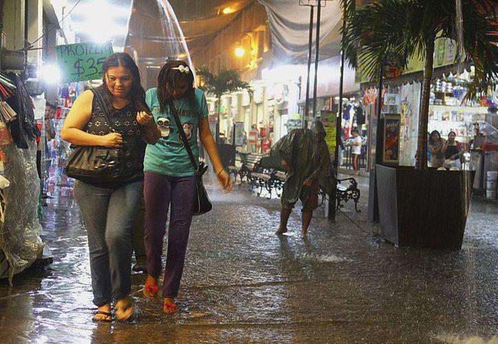 La lluvia sorprendió sobre todo por su intensidad y su duración a miles de meridanos que salían del trabajo. En la imagen, el pasaje Emilio Seijo en donde el agua se encharcó en algunas partes. (Juan C. Albornoz/SIPSE)